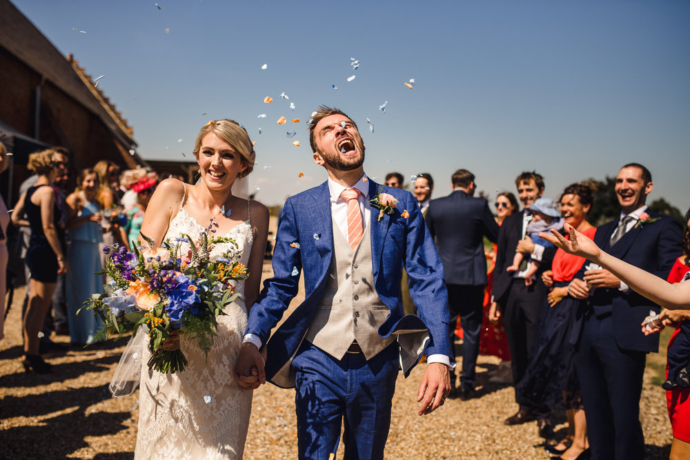 Kelly and Sam (scoffing the confetti!!!) after their humanist wedding ceremony at Copdock Hall, Ipswich. Image by   Matthew Lawerence