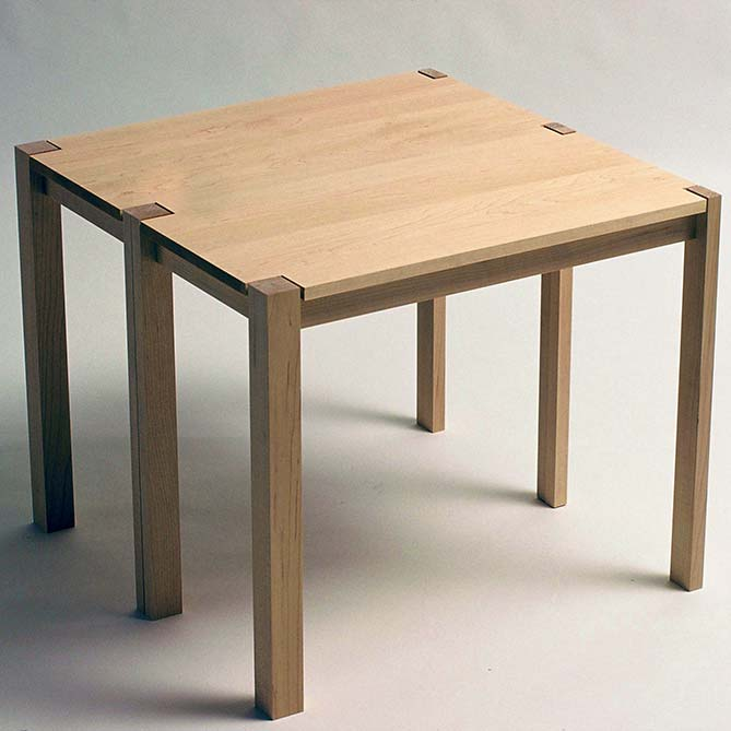 Concept - The versatile table bench is ideal for small living spaces. It can be used as a low table, or can easily be transformed into a rectangular bench.The table shown is in solid maple. No mechanical fixings are used to join the table. It relies solely on the shape of the tops of the legs to visually connect its two parts together.Table bench won first prize in the student section of the 15th International Furniture Design Competition, in Valencia, Spain in 1997, from a field of 270 international entrants.