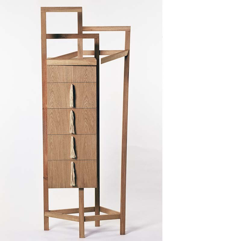 """Concept - The idea for the bedroom cabinet came from noticing how a piece of furniture designed to fulfil one function may be used for a completely different one. In this case how a chair in a bedroom may actually be used for hanging clothes.The frame of the bedroom cabinet is a de-constructed chair, and provides """"hooks"""" from which to hang clothes. The cabinet has five drawers for storing laundered clothes with tassel handles that refer to the clothing inside."""