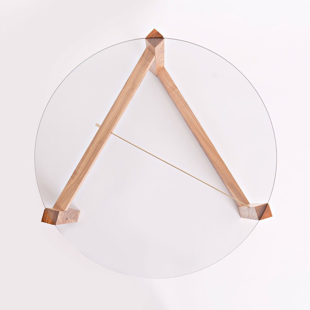 Concept - A simple line is drawn in space to define a triangular shape that is circumscribed by the circular glass top. The top of each leg is dovetailed to gently clasp the glass, which is then simply locked together by the tension of the brass rod.