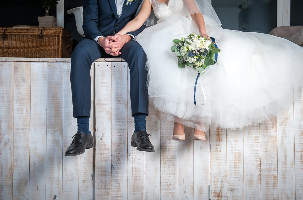 Bride and groom sitting on stage during post wedding photoshoot.