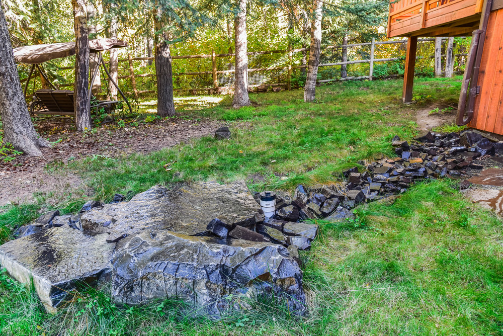 A backyard featuring stone pathways and staircases, bark nuggets and rock retaining walls in the Calgary and Banff area