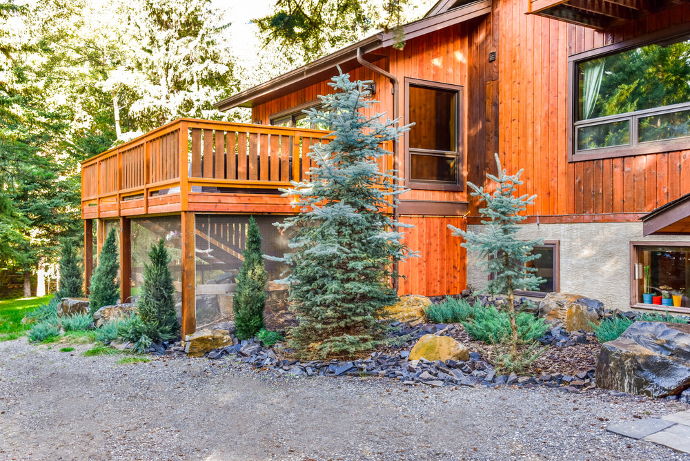 A backyard featuring stone pathways and staircases, bark nuggets, flagstone, and rock retaining walls in the Calgary and Banff area