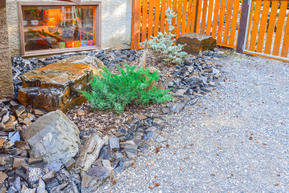 A backyard featuring a wooden gate and fence, bark nuggets and rock retaining walls in the Calgary and Banff area