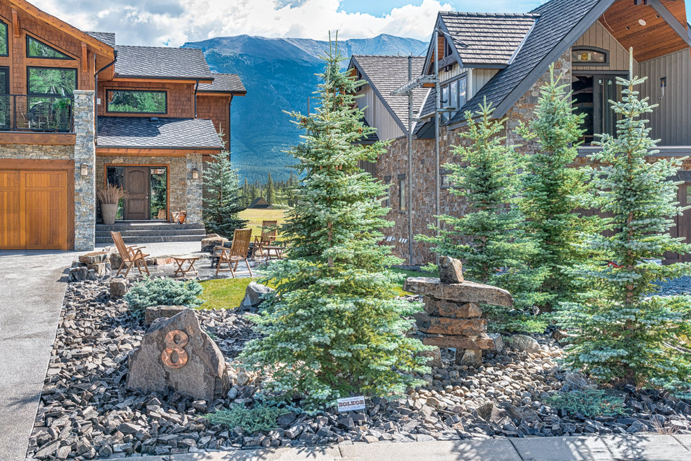 "A front lawn complete with a rock ""home number"" feature, a rock inukshuk, and a flagstone patio in the Calgary and Banff area"