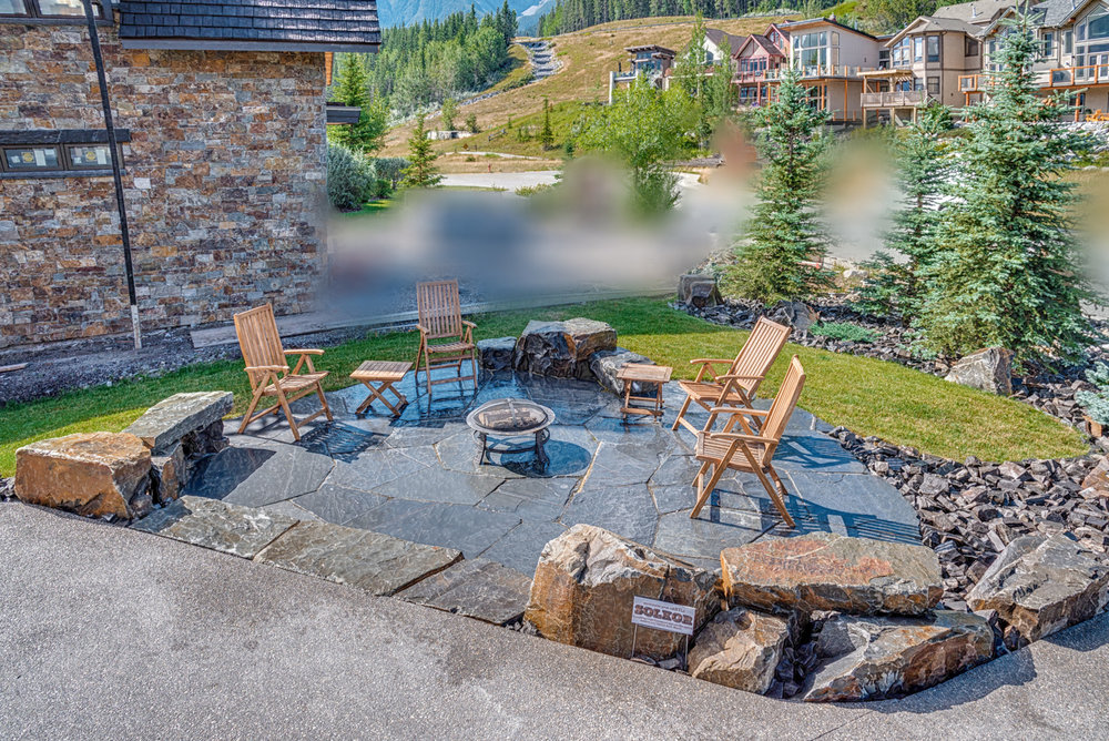 A flagstone patio featuring stone seating and steps in the Calgary and Banff area
