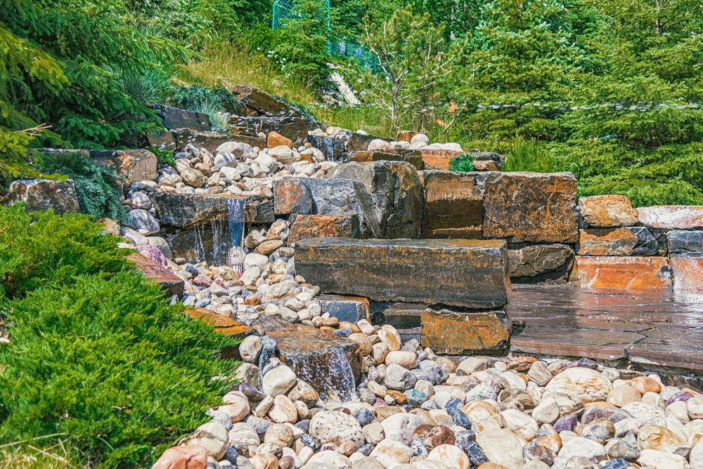 A low maintenance water feature complete with rundle stone steps, kootenay brown stones and river rock in the Calgary and Banff area
