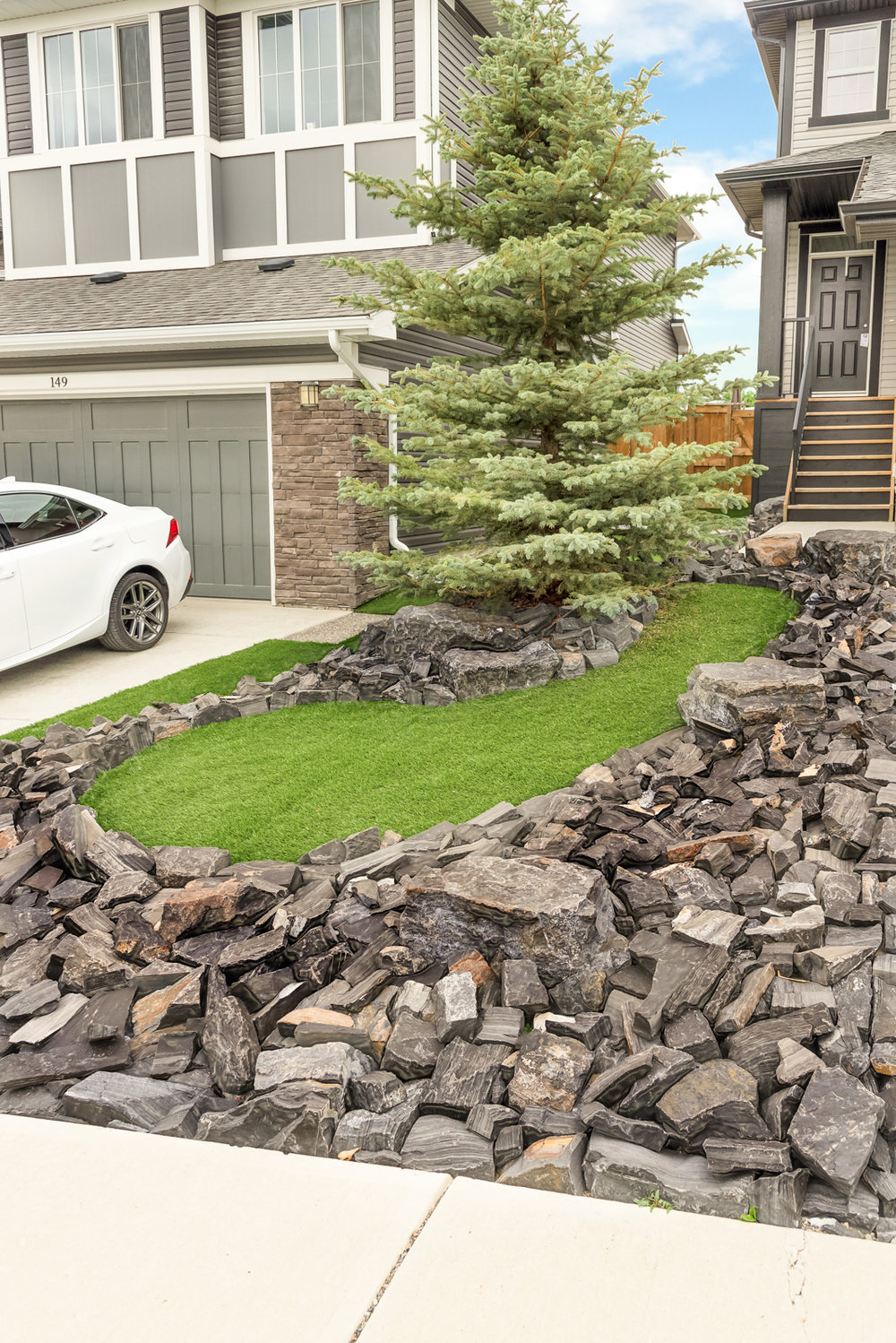 A front yard featuring synthetic grass and rundle stone tailings in the Calgary and Banff area