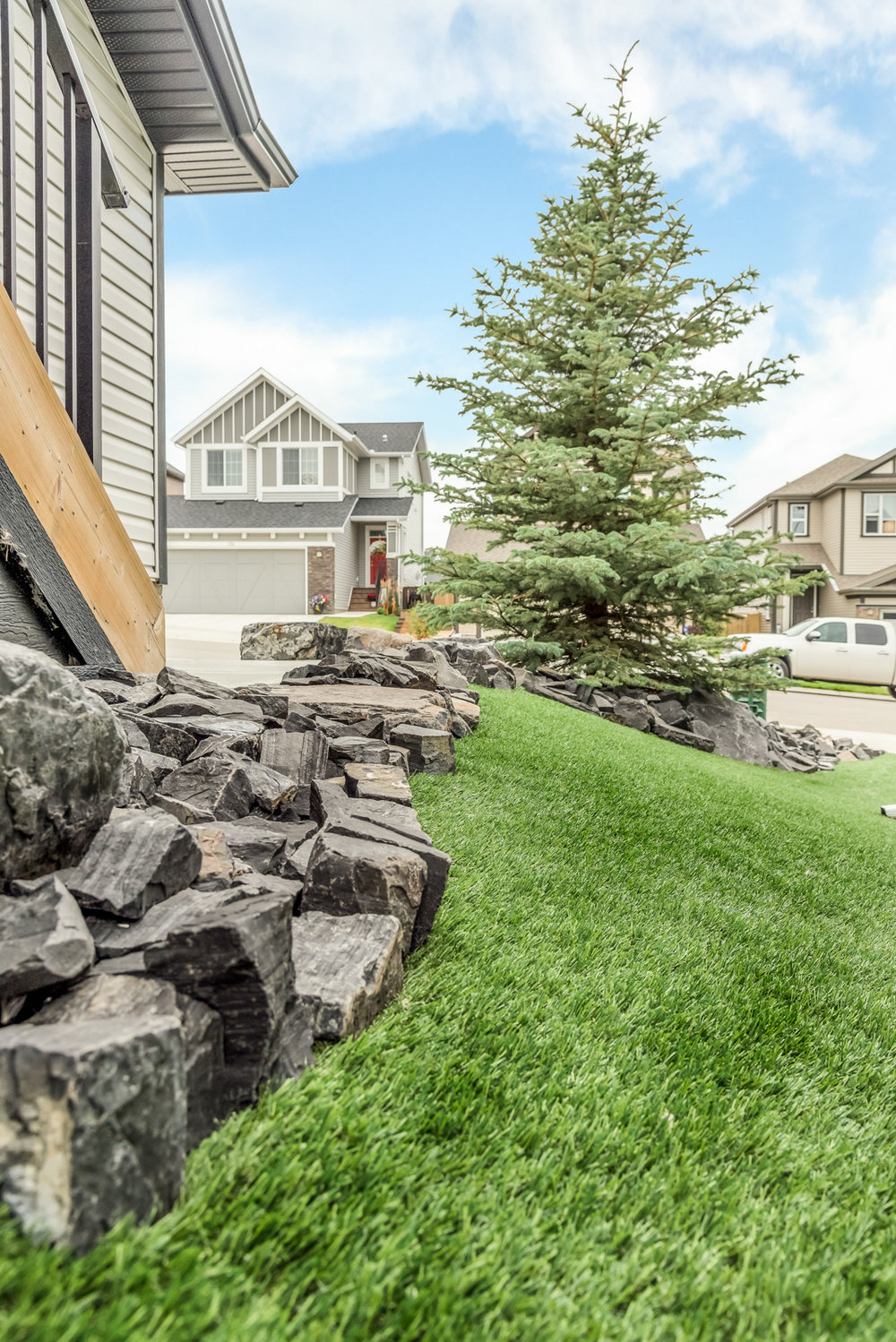 A side yard featuring synthetic grass and rundle stone tailings in the Calgary and Banff area
