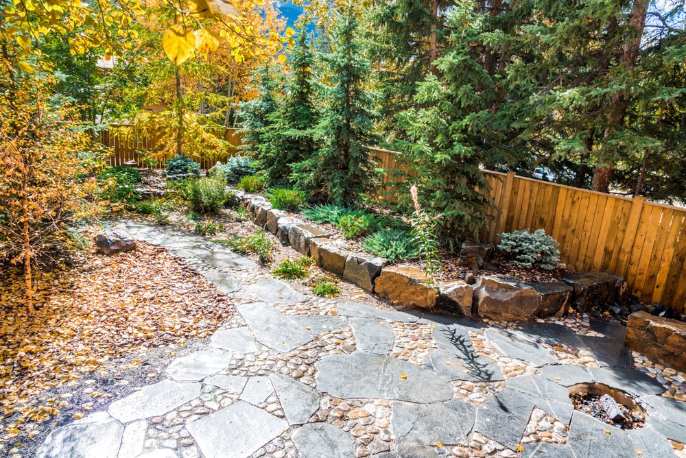 A river walk patio and walkway featuring shrubs, trees, natural stone seats and low maintenance rundle stone tailings in the Calgary and Banff area