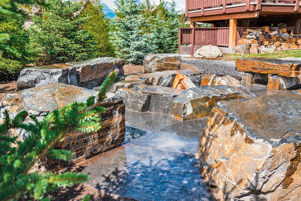 A back garden complete with waterworks, birch trees and spruce trees in the Calgary and Banff area