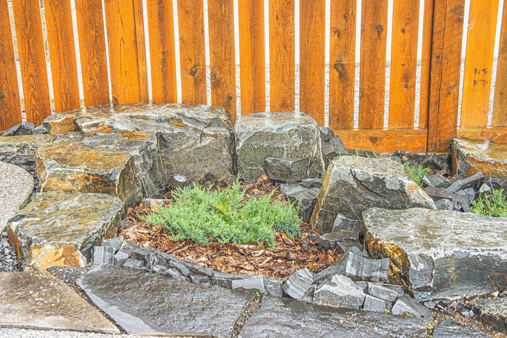 A backyard featuring maintenance-free stoneworks and wooden fencing in the Calgary and Banff area