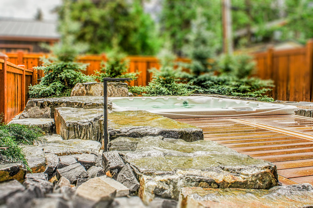 A patio complete with a sunken hot tub stone feature in the Calgary and Banff area