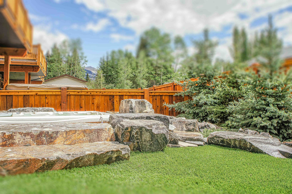 A wide-angle image of a backyard featuring maintenance-free stoneworks, fencing, a sunken hot tub feature, and tree installs in the Calgary and Banff area