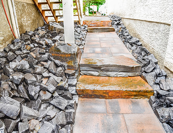 A stone pathway by the side of a house - complete with additional drainage solutions - in the Calgary and Banff area