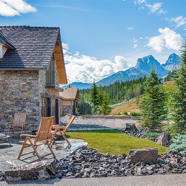 A backyard patio featuring rock works and deck chairs in the Calgary and Banff area
