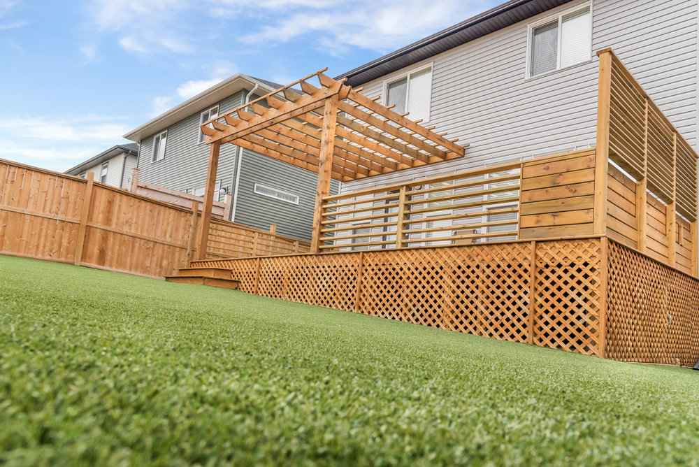A wooden deck complete with railings, integrated seating and privacy louvres in the Calgary and Banff area