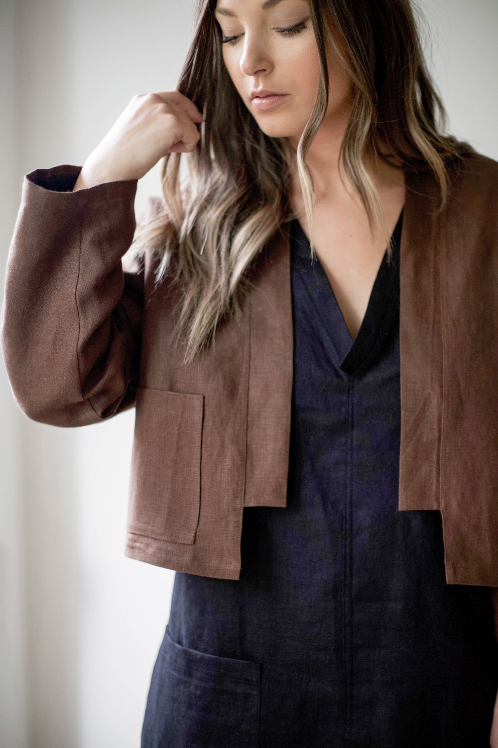 nomi-designs_ann-jacket_chocolate-colored-natural-linen-jacket_front-pocket-detail_paired-with-linen-dress.jpg