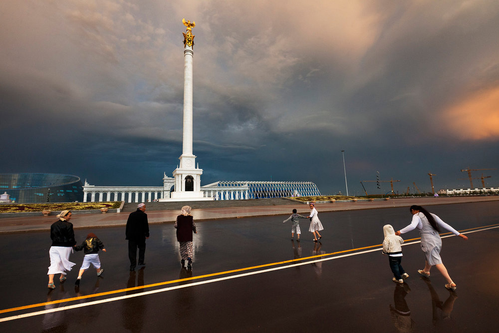 The alabaster-white pillar known as the Samruk monument is topped by a golden eagle, one of many nationalist symbols in Astana. The Samruk is a beacon for visitors like these ethnic Kazakhs from the southern city of Taraz.  Astana, Kazakhstan