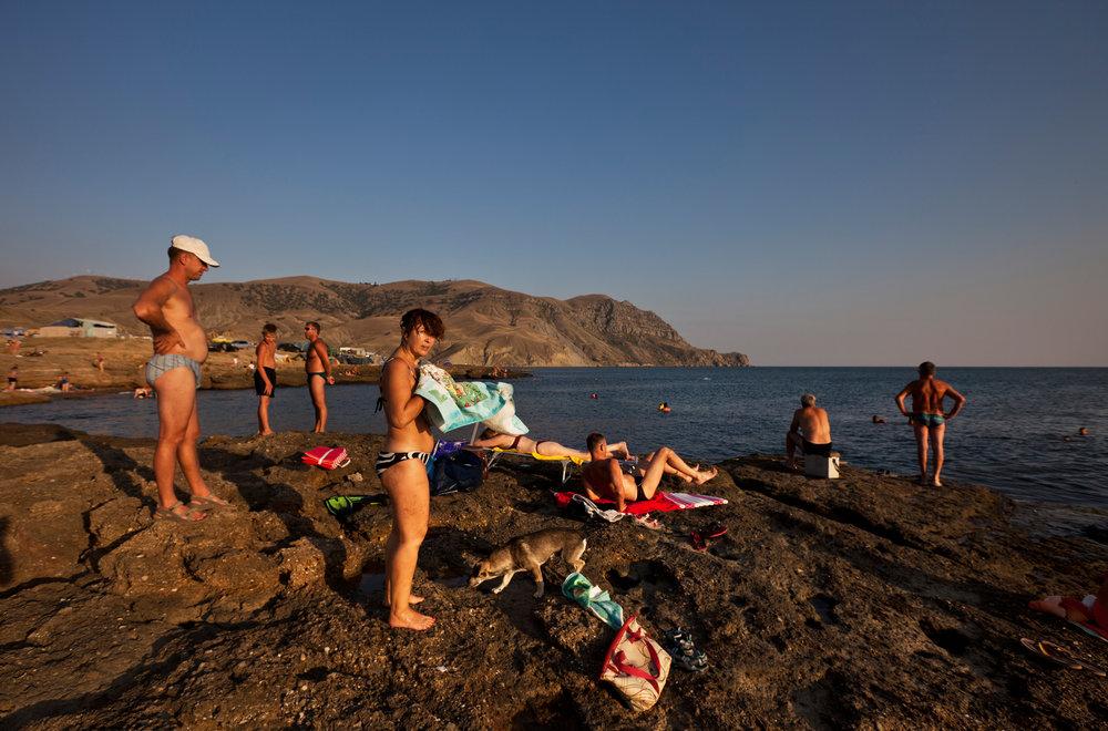 Tourists sunbathe and picnic at beach in Maganom, north of Sudak.  Meganom, Crimea