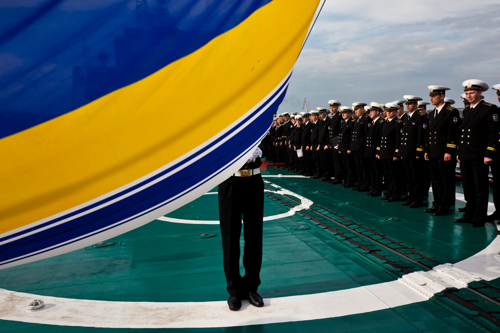 A Ukrainian Black Sea Fleet Navy soldier hoists his country's flag during the routine morning salute.  Sevastopol, Crimea