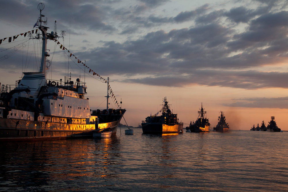 The setting sun reflects off of several Russian Black Sea Fleet warships anchored in the bay of Sevastopol. During the Day of the black Sea Fleet they took part in a in the port of Sevastopol.  Sevastopol, Crimea