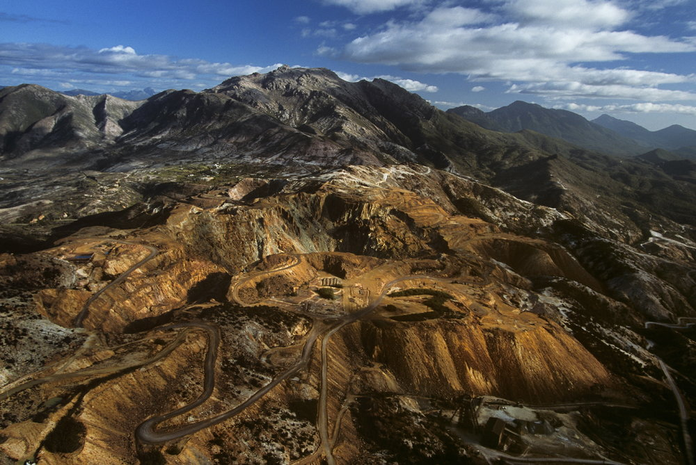 Aerial view of the Mount Lyell area near Queenstown, Tasmania, in Australia showing deep eroded gullies and bare multicolored hills due to open cut mining.  Queenstown, Tasmania