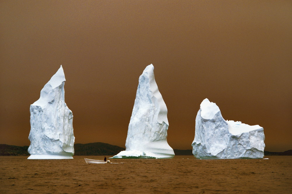 "A trio of icebergs cast in the eerie glow of a nearby forest fire in ""The Iceberg Capital of the World.""  Twillinggate, Canada"