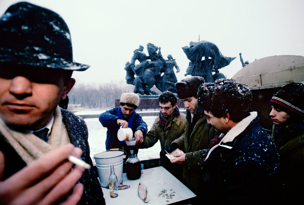 A smoking sentry stands guard as his partners sell shots of homemade wine to thirsty Muscovites. With the end of the Soviet era, these moonshiners from the Caucasus were free to bring their business to the Russian capital.  Moscow, Russia