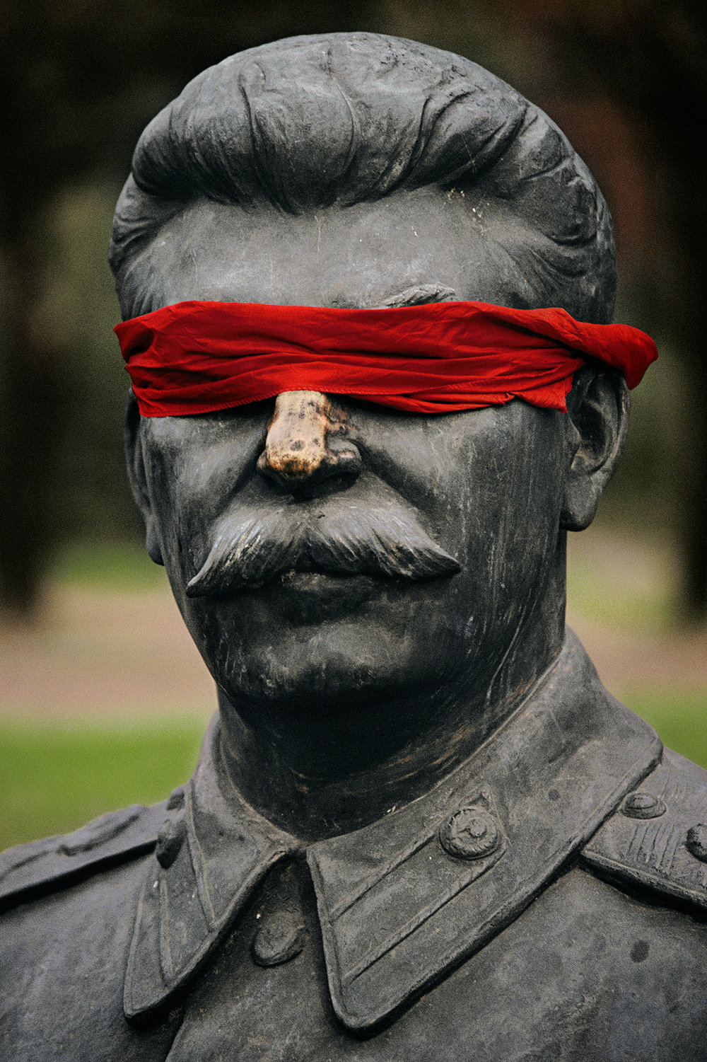 Blindfolded by a child, a statue of Stalin, most feared ruler of the communist era, sits amid other toppled effigies of party leaders now jumbled together in a Moscow park.  Moscow, Russia