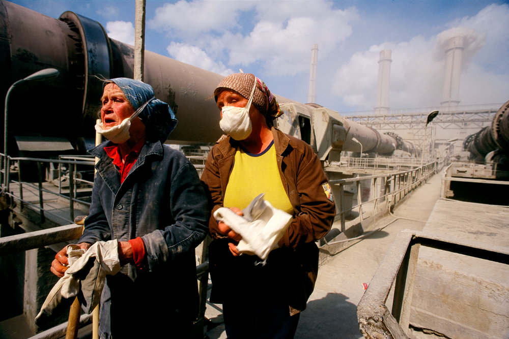 Workers take welcome breaths after a shift in the dust-filled confines of their cement plant. Exposure to the pollution leaves them exhausted at day's end.  Kunda, Estonia