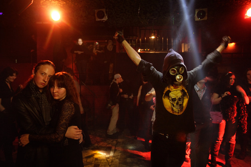 "2:55AM - Saturday night is ""goth night"" at club Relax. The goths are known for their bleak and sardonic perspectives; this teen's mask is a homage to a terrorist attack in the same building where the use of gas left many dead."