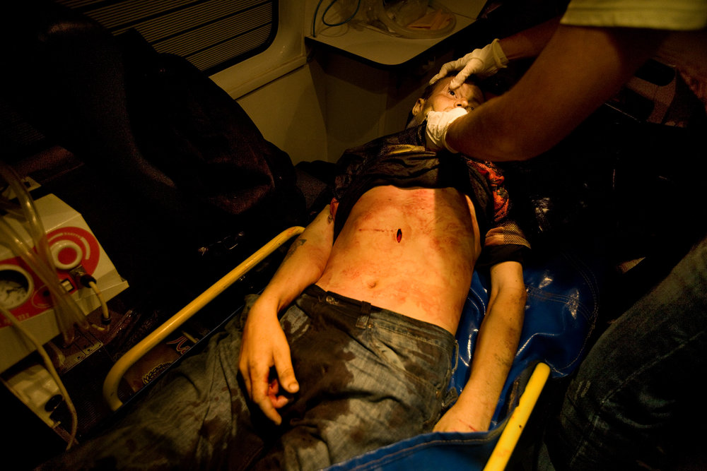 11:52 AM - Medical personnel examine a stab-victim discovered in a police raid in the eastern district of Moscow.