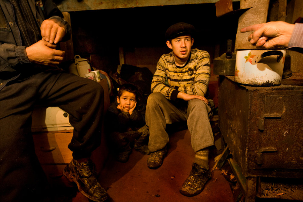 5:52 PM - A family in their bleak make-shift home in Chelobityevo, 'gastarbeiter' colony on the outskirts of Moscow.