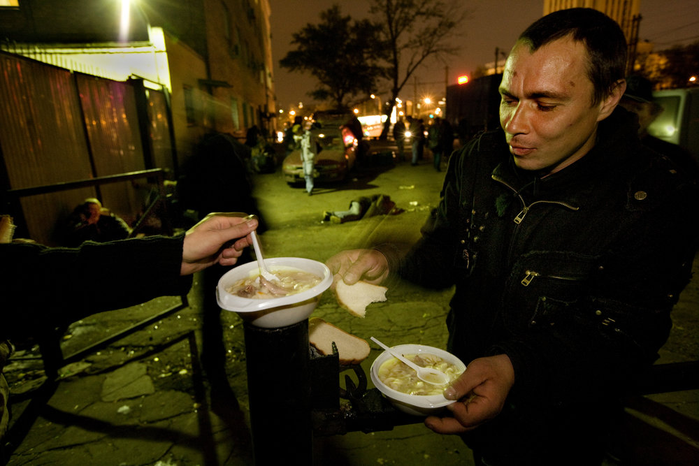 9:19 PM - A mobile food kitchen stops outside a train station to deliver warm soup and bread to the homeless.