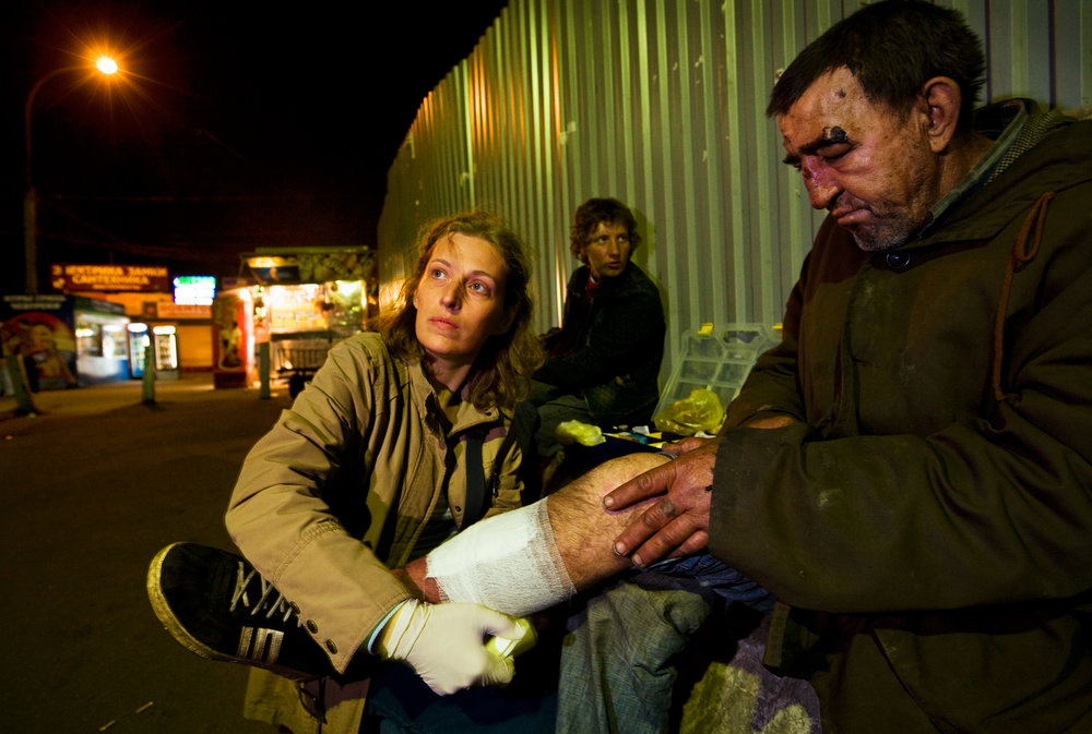 10:45PM - Angel of the night, volunteer Tatyana Sveshnikova, attends to a battered homeless man near Kursk Station with aid collected from personal friends and family.