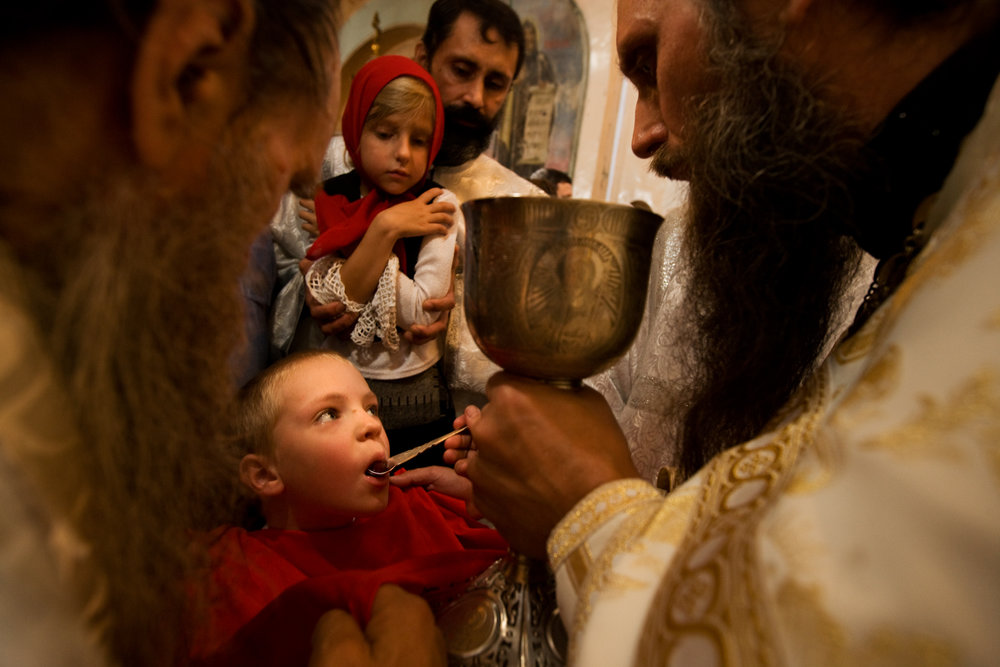 For an early taste of religion, a child receives Communion wine from Father Sergy at the Znamensky Cathedral.  Tyumen, Russia