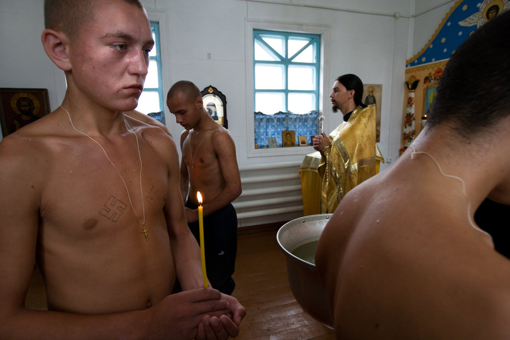 Praying that the cross will replace the swastika in a young criminal's heart, Father Oleg gathers inmates for baptism at a juvenile prison.  Bogandinskoye, Russia