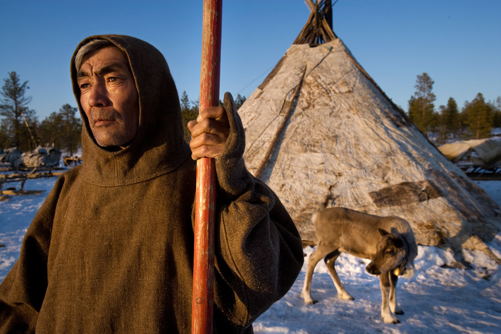 Nenets herder, Alexander Turgachev, in front of his brigade's chum - a traditional dwelling (yurt) made of reindeer skins.  Near Saranpaul, Russia