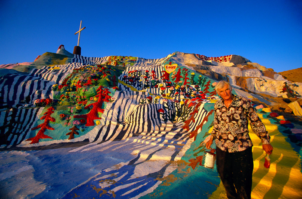 "Leonard Knight, 71, has redesigned the desert landscape with adobe, straw, and thousands of gallons of paint. ""Salvation Mountain"" is now a national folk art shrine.  Niland"