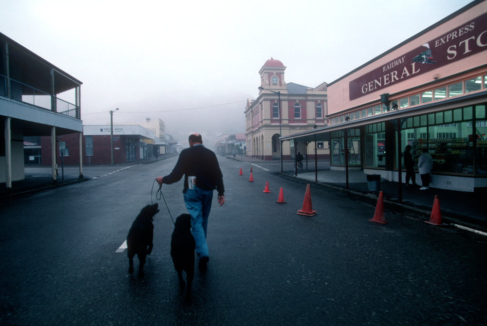 Heading for the coffeshop with dogs on the leash, a pedestrian crosses Main Street in early morning mist.  Queenstown