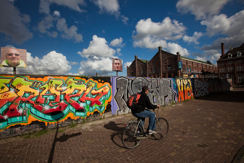 A cyclist bikes past graffiti at the corner of Linnaeusstraat and Praetoriusstraat in Amsterdam.