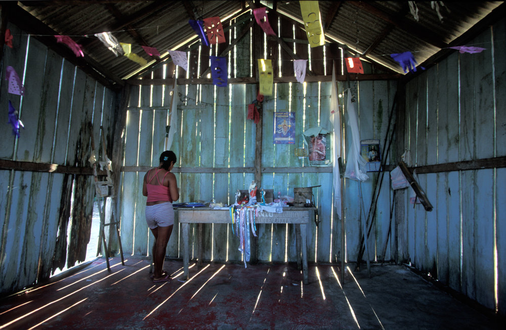 In the village of Niteroi in Kwata-Laranjal, a woman prepares the altar of a makeshift church for a ceremony honoring the patron of the village. Many of the Munduruku have converted to Christianity.  Niteroi, Brazil