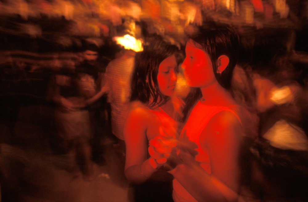 """Western cultural influences dominate the """"Disco Night"""" in Niteroi, as two young Indian girls slow dance to the sound of music, blasting from a simple set of speakers.  Niteroi, Brazil"""