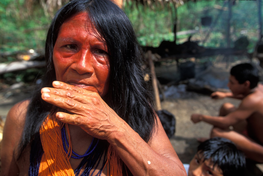 Paroripa, the village chief's wife, wipes her face after a feast. She wears the traditional 10 meter long Waiapi necklace made of approximately 4,000 beads.  Aramira, Brazil