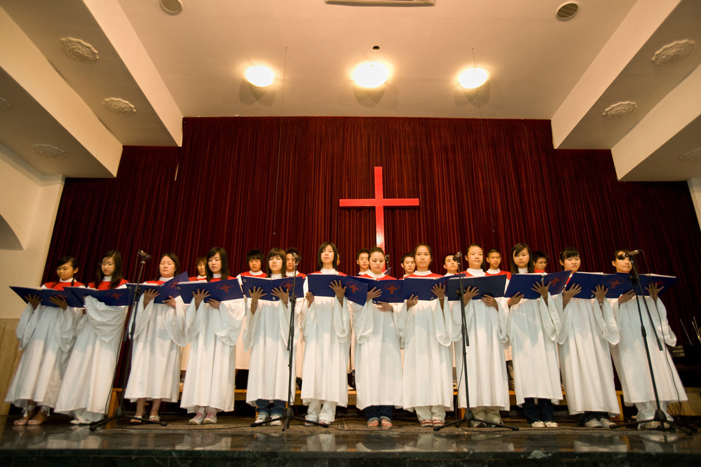 Chinese parishioners gather for service, including choir performances, at a Christian church in Prato.