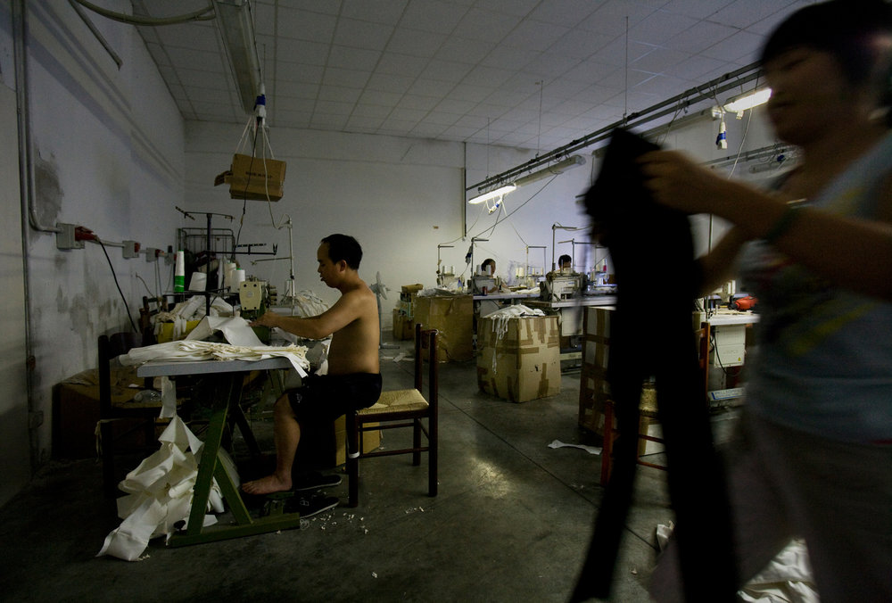 "The success of the ""Chinese Pronto Moda"", or ""ready-to-wear"", factories is based on a disregard for standard labor laws. Employees, often including families with young children, live communally in factory warehouses, often working round the clock until piece orders are filled."