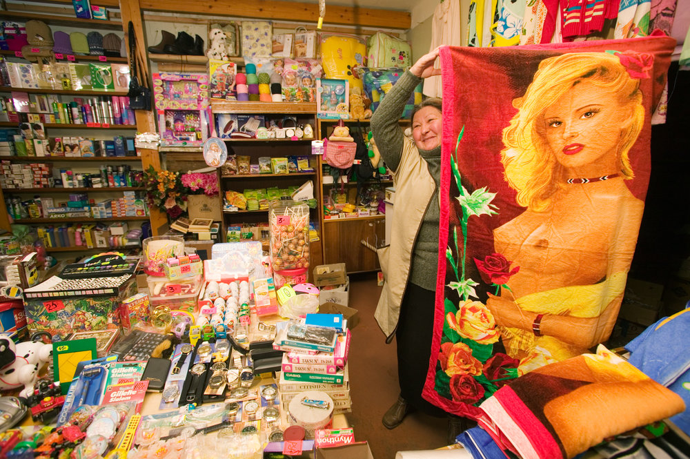 An Aleut sales clerk displays merchandise typical of the few shops available in Nikolskoye.  Bering Island, Russia