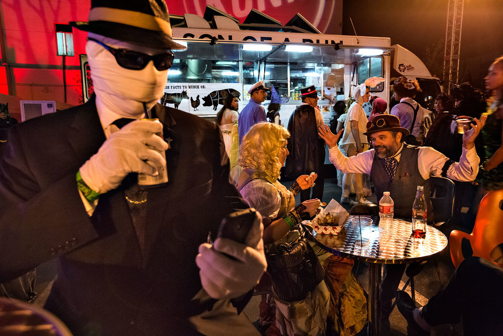 Halloween partiers enjoy freshly made meals from food trucks at public radio KCRW's annual masquerade ball. The fundraiser features several bands and is held on the grounds of the LA Park Plaza hotel. Special events guarantee customers – and cash – for area food truck businesses.  Los Angeles, CA.