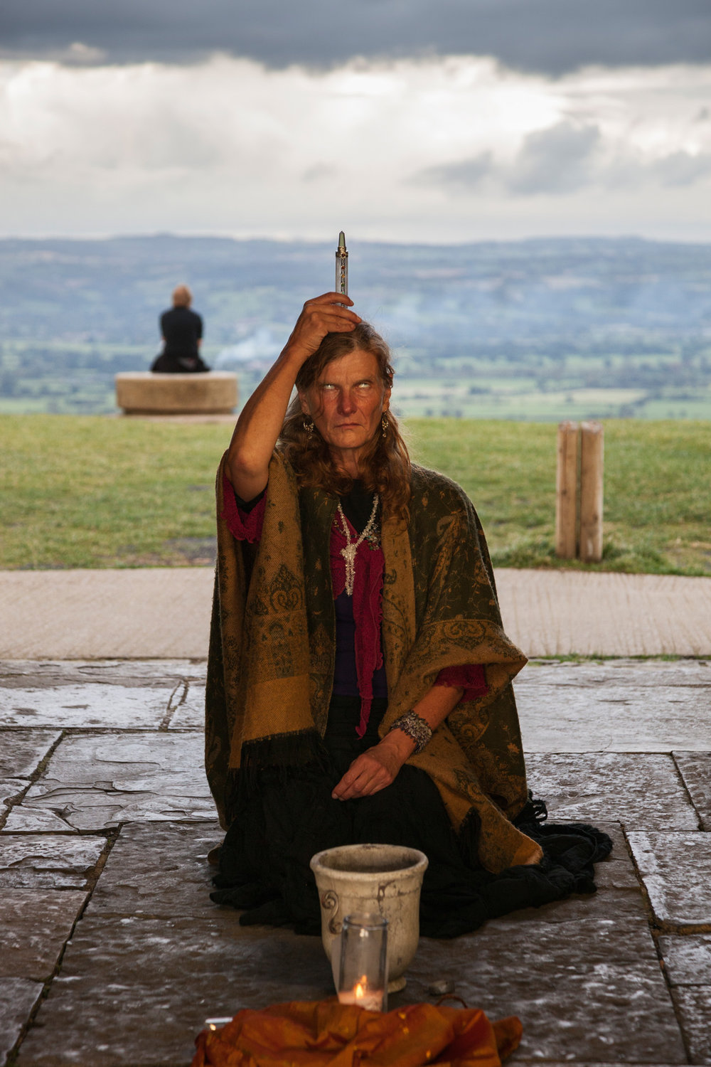 A woman performs a ritual inside the bell tower on Glastonbury Tor, believed to be the mythical entrance to Avalon, the land of fairies. For centuries, people in Glastonbury believe the legendary island of Avalon to be the final refuge for the wounded Arthur.  Glastonbury, England.